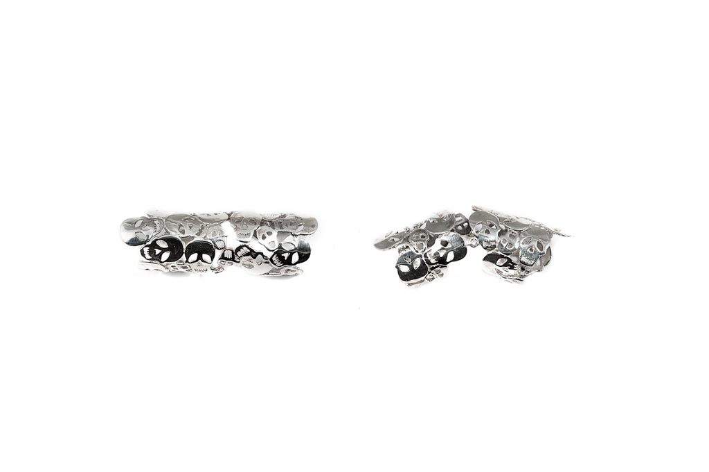 Articulated silver ring with skulls